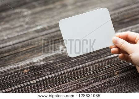 holds card with text on old wood plate