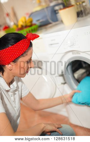 Young woman has a laundry day at home she takes the laundry out of your washing machine