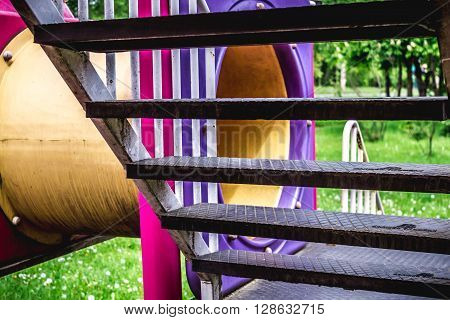 Shot made through the stairs of a slider from a kids playground with a tube to hide and trees and grass in background