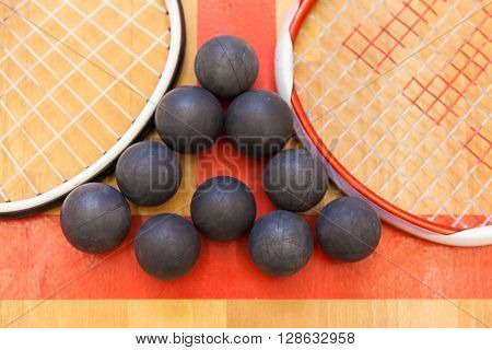 squash balls between two squash rackets on the court