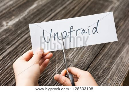 holds card with text unafraid on old wood plate