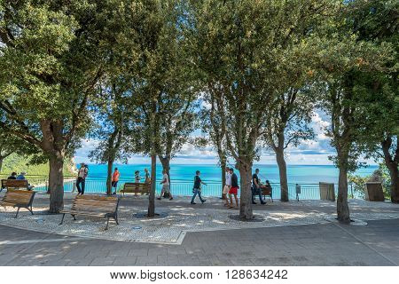 Sirolo Italy - August 20 2016: panoramic boardwalk with tourists in Sirolo Italy. Sirolo village features a medieval town centre which culminates in a square with view on the adriatic sea and on Mount Conero.