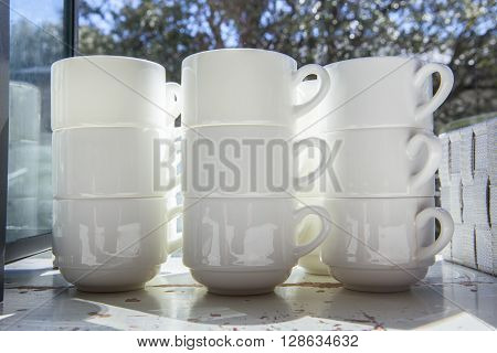 White cups for coffee and tea piled on vintage table close to window open to garden area
