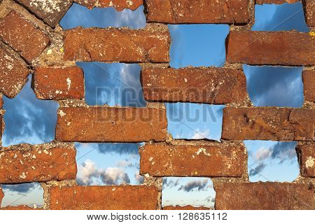 View of the evening sky with thunderclouds through holes in an old brick wall