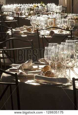 Wedding tables full of glint dishware against the sunlight