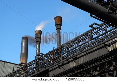 Smoke and steam from industrial chimneys escaping to atmosphere.