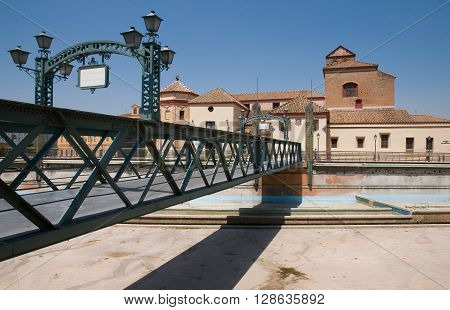 Bridge Puente de Santo Domingo in Malaga with traditional architecture on background.