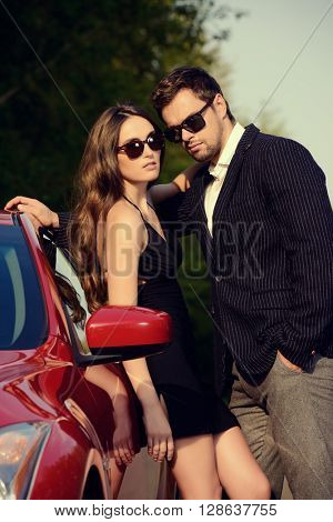 Beautiful couple near the car. Beauty, fashion. Love concept.