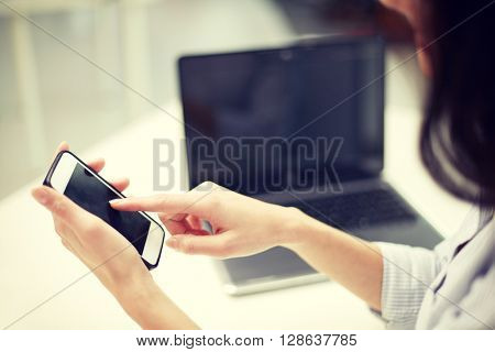 business, technology and people concept - close up of woman hands with laptop computer and smartphone texting message at office