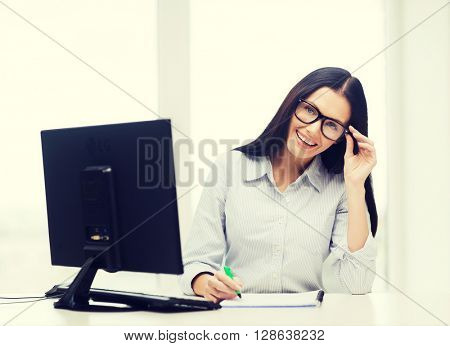 education, school, business and technology concept - smiling businesswoman or student wearing black eyeglasses