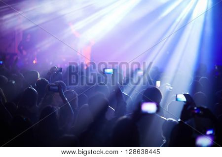 People listening to the singer recording him with smartphones
