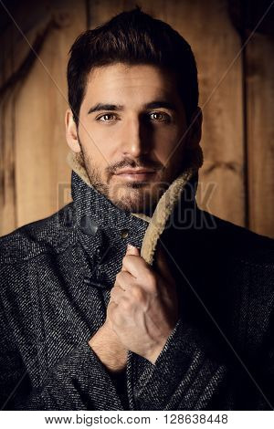 Vogue shot of a handsome male model in a coat standing by a wooden wall. Men's beauty, seasonal fashion.