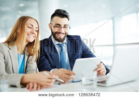 Happy businessman with his female colleague using touchpad
