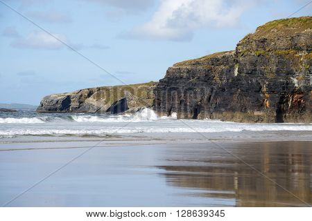 beautiful soft waves break on the beach cliffs at ballybunion