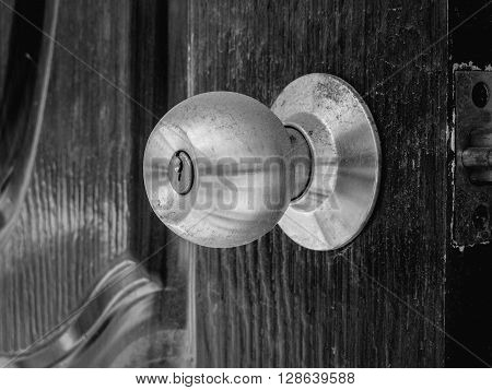 Dusty old door knob on open wooden door black and white effect