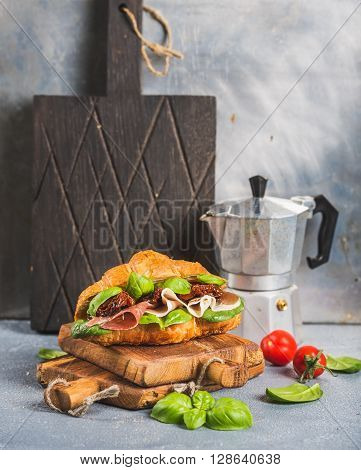 Croissant sandwich with smoked meat Prosciutto di Parma, sun dried tomatoes, fresh spinach and basil on stone textured grey background, dark cutting board and moka coffee pot behind, selective focus