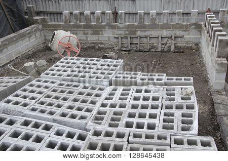 many neatly folded gray cinder blocks background closeup. concrete mixer.