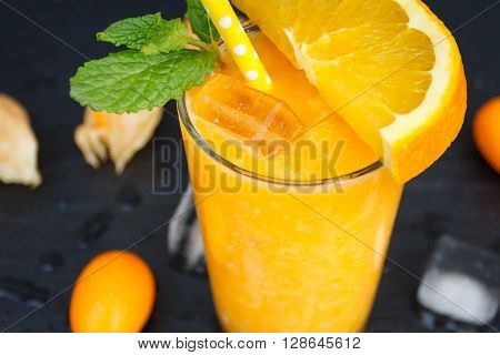 Orange smoothie in glass with yellow straw fresh fruit slice kumguat and perrepmint