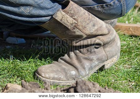 old fashioned work boots kneeling man boots