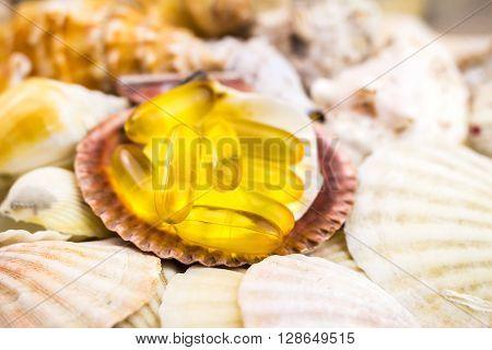 Fatty acid omega 3 capsules on the beautiful mixed seashells background