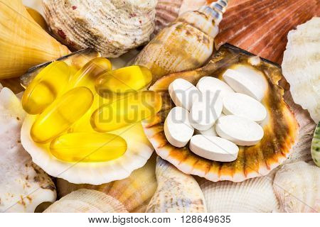 Calcium pills and omega 3 capsules natural food supplement on the beautiful seashells background