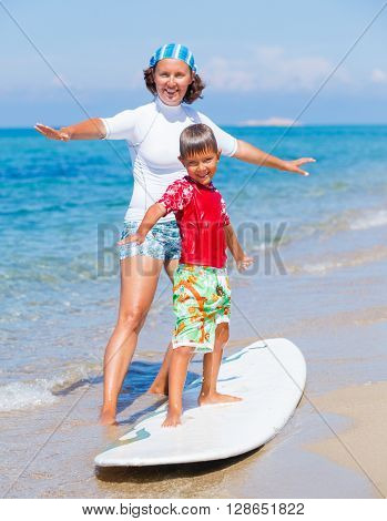 Little boy with his mother learning surfing