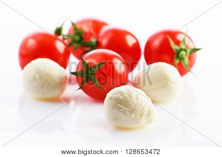 three mozzarella cheese balls and five ripe cherry tomatoes on the white background. horizontal format