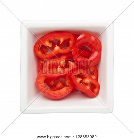 Sliced red bell pepper in a square bowl isolated on white background
