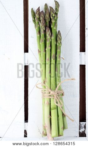 Simple composition . Organic asparagus tied with brown string in a rustic white painted wooden crate