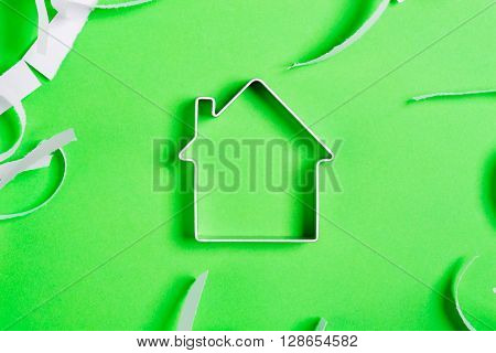 Metal House Standing On A Green Surface With Teared Paper Pieces