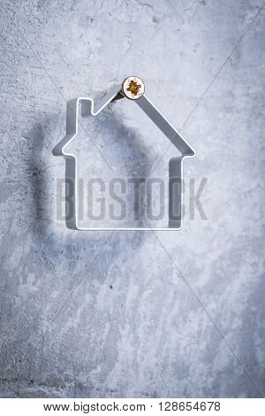 Metal House Hanging On The Screw In The Grey Concrete Wall