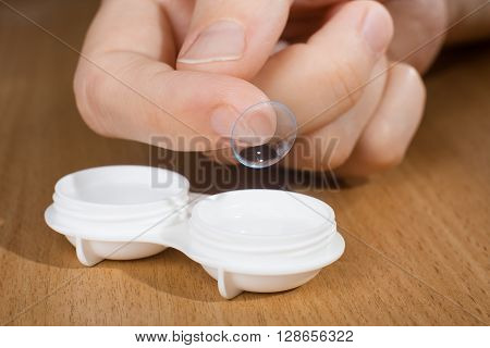 hand of woman holding contact lens closeup