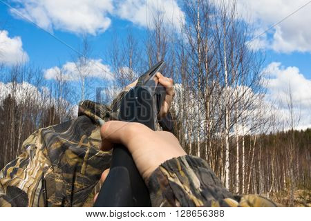 hands of hunter in camouflage shooting from a gun