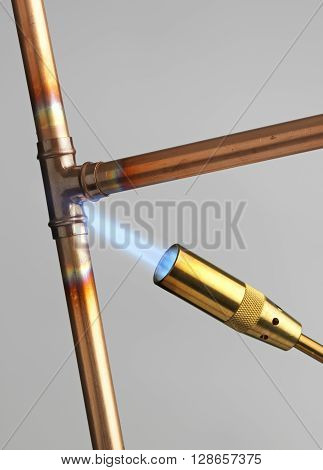 Blowtorch and copper pipe with flame on a grey background