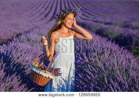 Beautiful young girl with basket in the lavander fields in Valensole. Provence, France.