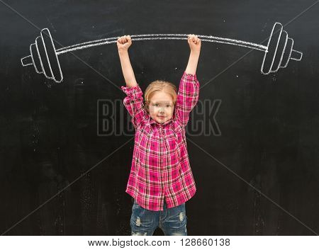 lovely little girl rising up drawm on the blackboard barbell with two hands