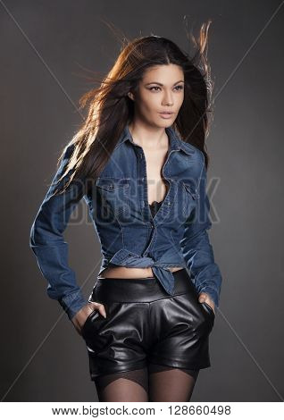 Brunette woman in leather pants and jean jacket on a gray background.