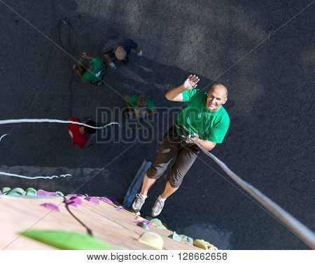 Positive Mature Extreme Climber Greeting Waving Hand Hanging High on Belaying Rope on Outdoor Rock Climb Gym