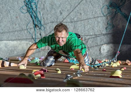 Portrait of Handsome Adult Male Climber Moving Up on Sport Training Course in Outdoor Climb Gym Using Rope Belaying Gear with Positive Inspired Face Emotion