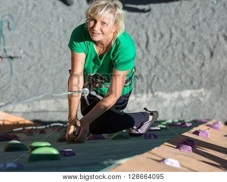 Portrait of Adult Female Climber Moving Up on Sport Training Course in Outdoor Climb Gym Using Rope and Belaying Gear
