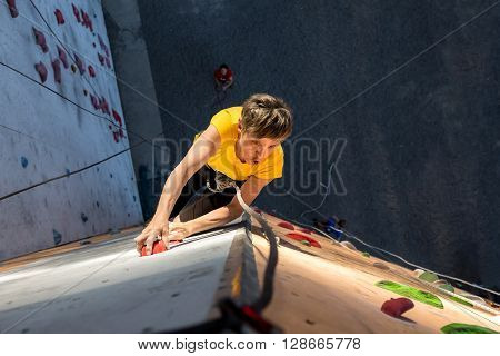 Elderly Female Climber Makes Hard Move on Outdoor Climbing Wall Sport Competitions High Up above Ground Belaying People on Remote Background