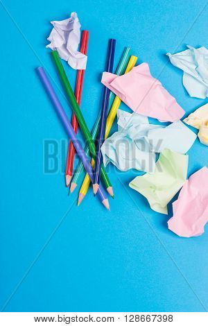 Several Color Pencils With Crumpled Color Paper Over The Blue Background