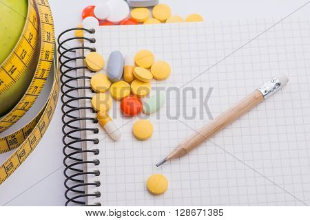 Fresh Green Apple With Notebook, Measuring Tape And Pills