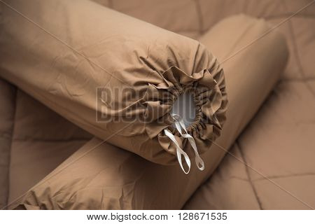 Close up of brown bolster on the brown blanket.