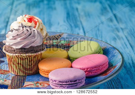 Few Tasty Cupcakes With Macaroons On Plate