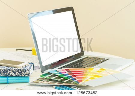 designer's working table - open notebook with  colour charts, copy space on blank screen