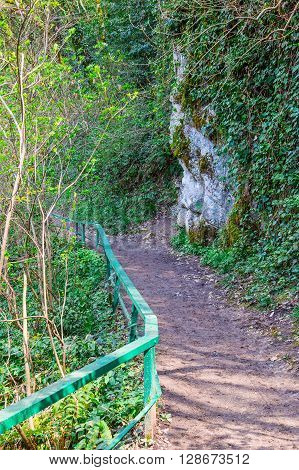 Mountain trail with fence leading up along steep wall