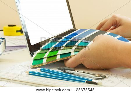 designer's working table - close up of designer hands holding colour charts, copy space on emptyy screen