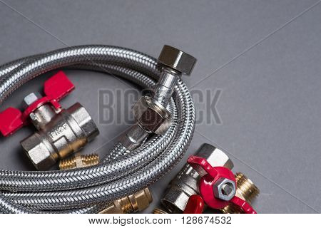 Assorted Plumbing Fittings And Hose On Grey