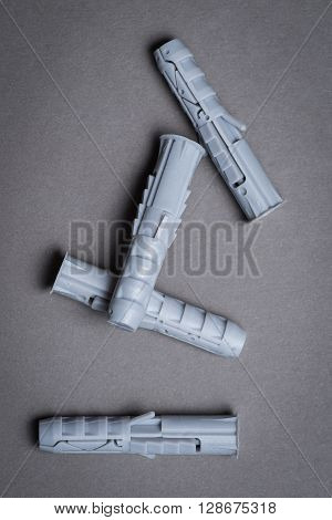 Four plastic dowel on a grey surface